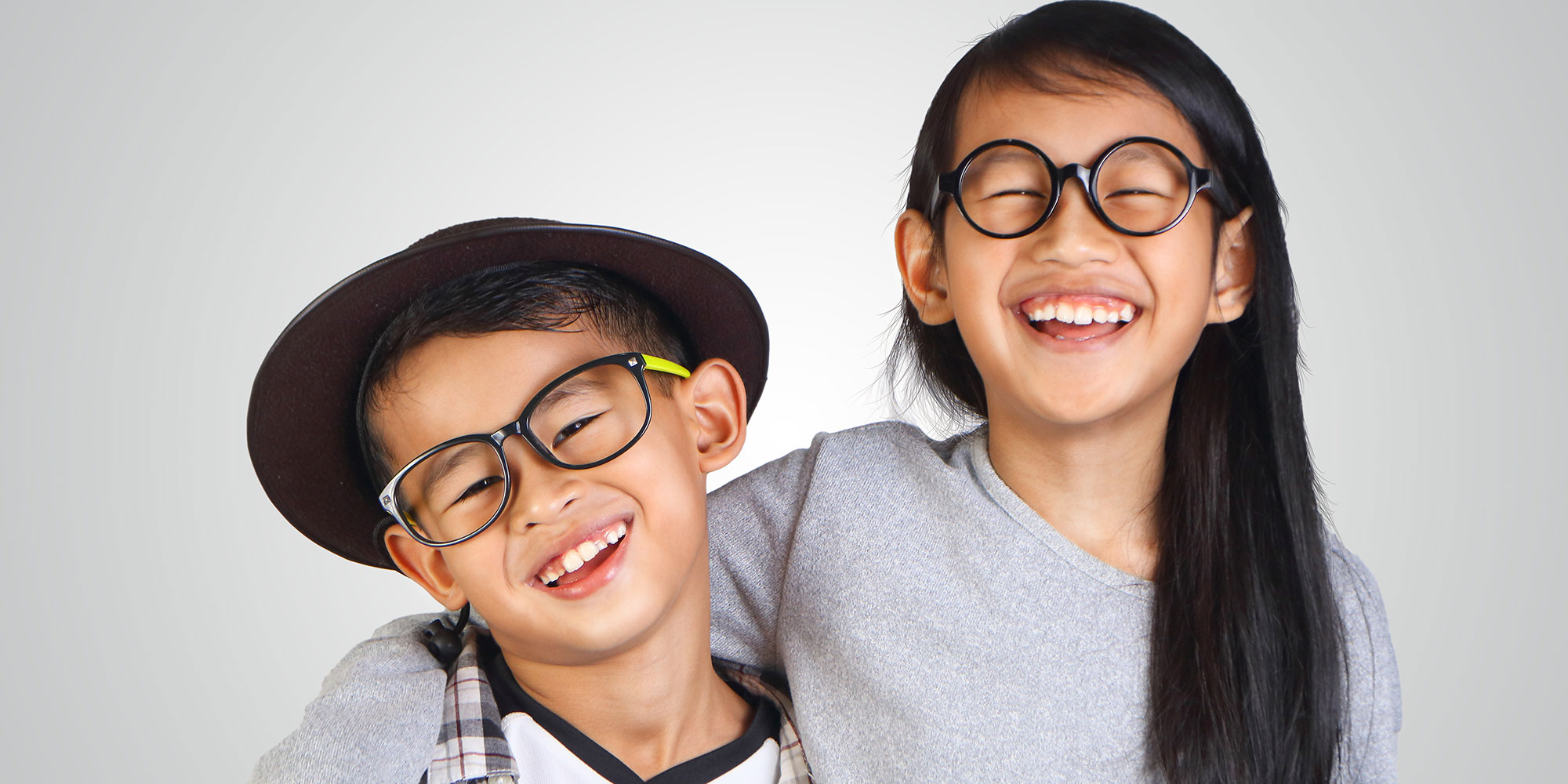 Two kids laughing and wearing fun glasses