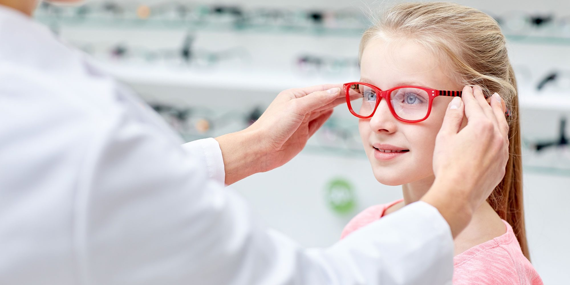 A young girl trying on glasses frames with an optician in an optical shop