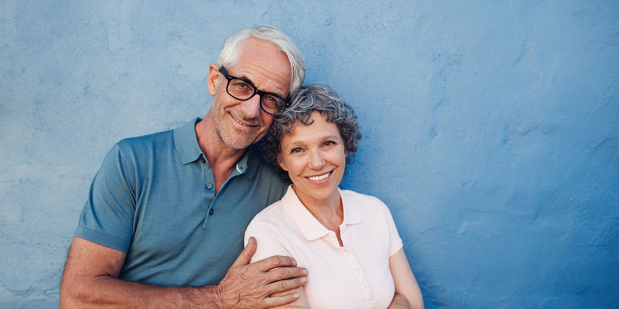 A middle aged couple smiling and standing together against a blue wall