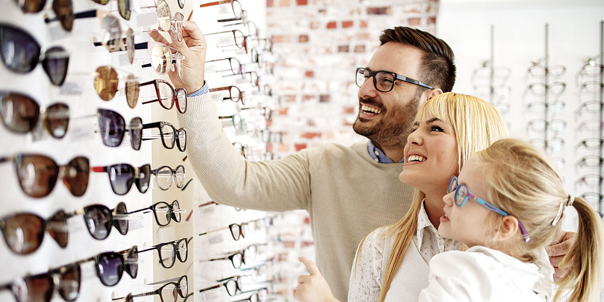 Young family picking out glasses frames in an optical shop